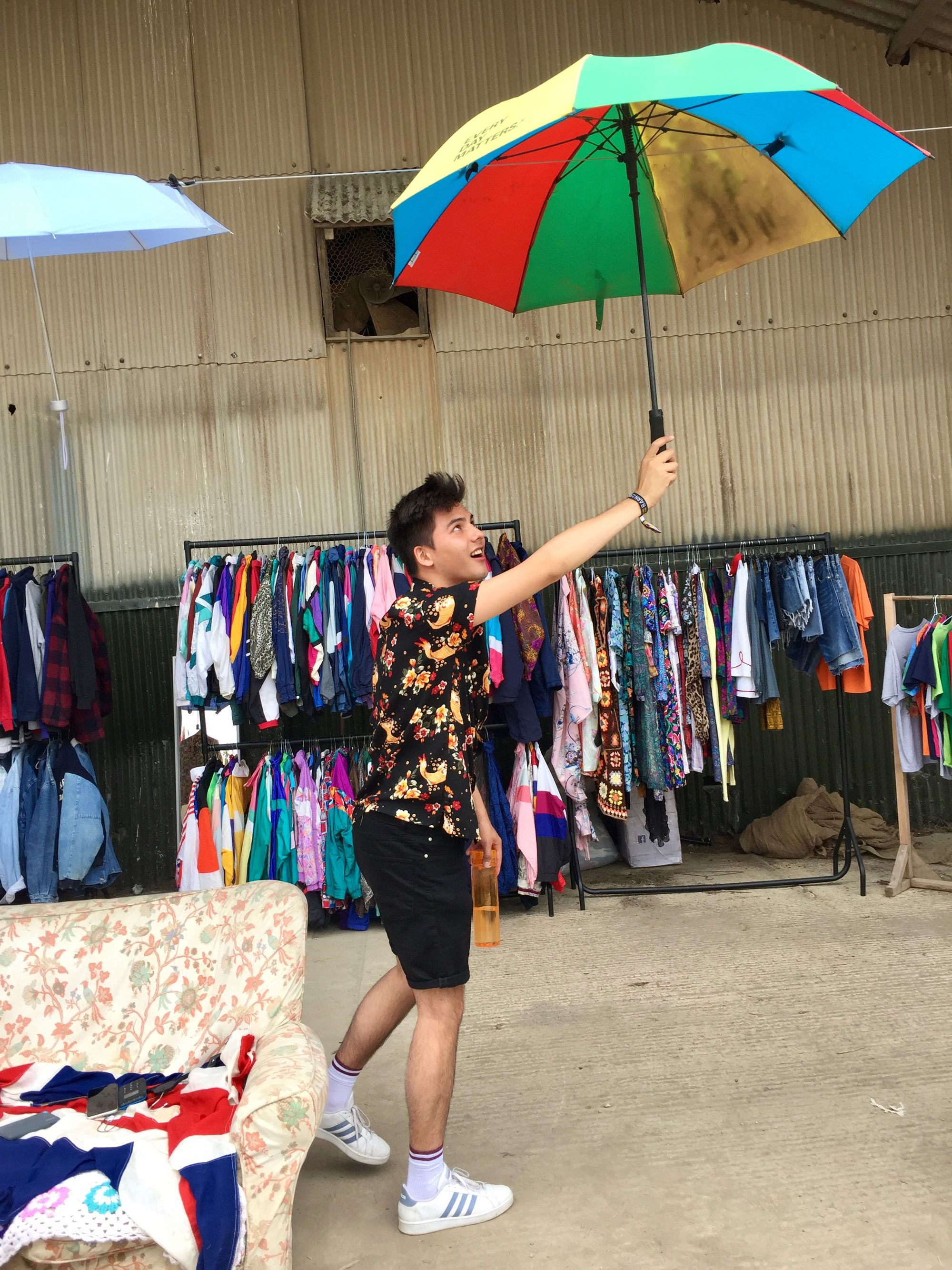 Chris at a festival, holding an umbrella and water bottle against a backdrop of vintage clothing