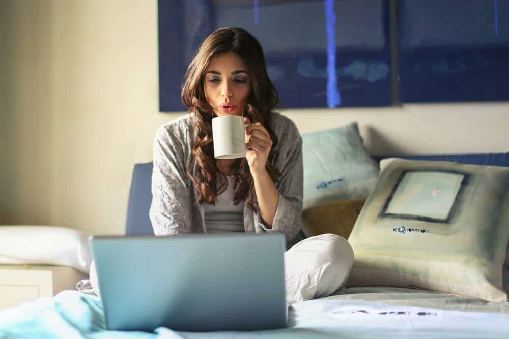 woman-in-grey-jacket-sits-on-bed-uses-grey-laptop-935743-3365753