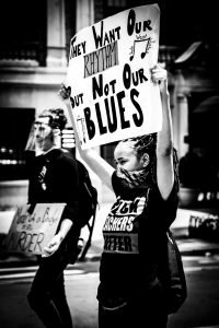 african-american-woman-holds-sign-at-black-lives-matter-protest-wearing-mask-during-the-corona-virus-in-city