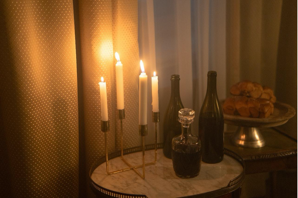 A table with wine and lit candles.