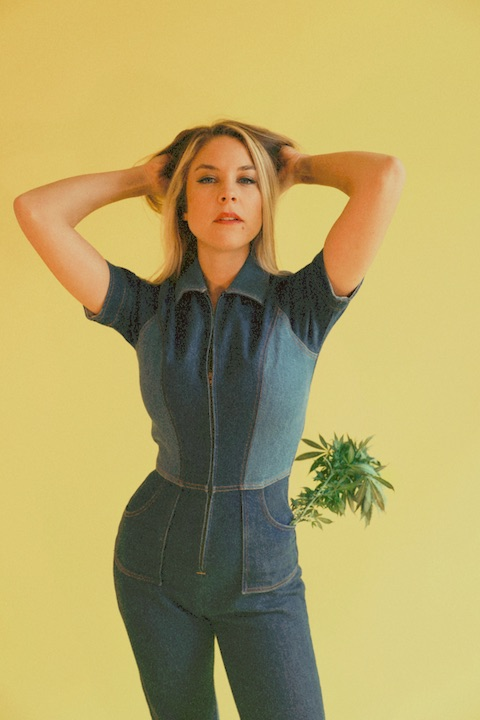 Brooke with her hands in her hair and a cannabis plant in her pocket.