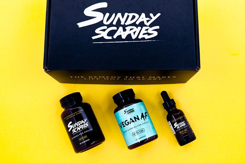 A black sunday scaries box with a bottle of gummies, a bottle of gumdrops and a bottle of tincture underneath it.